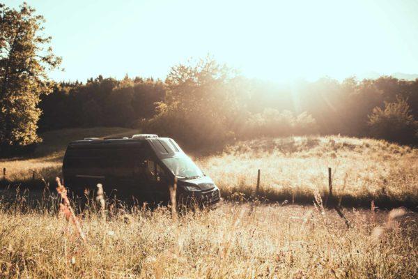Campingbus fährt durch herbstliche Landschaft