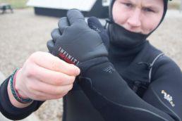 Ein Kiter zieht Handschuhe an