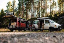 Zwei Campingbusse in einem Wald in Norwegen
