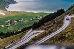 Ein roter Campingbus fährt an einem Fjord in Norwegen vorbei